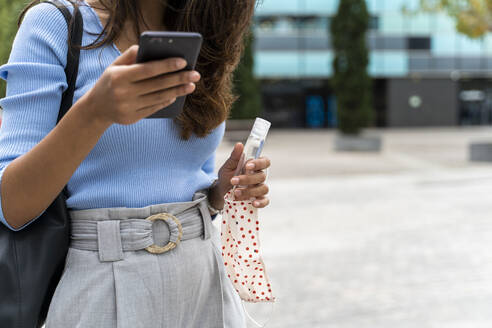 Woman with protective face mask and sanitizer using smart phone in city during COVID-19 pandemic - AFVF07560