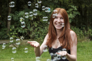 Happy woman playing with soap bubbles in backyard - LBF03260