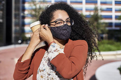 Woman wearing protective face mask while holding reusable bamboo cup in city during sunny day - VEGF03099