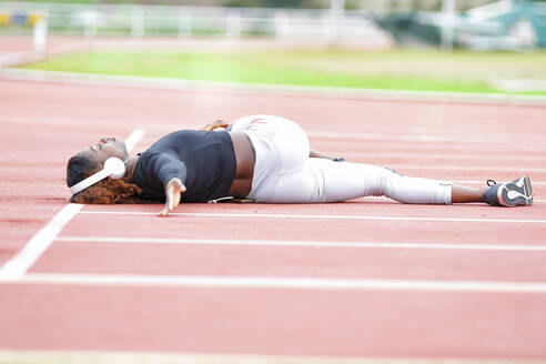 Sportswoman doing stretching exercise while lying down on runner track - GGGF00051