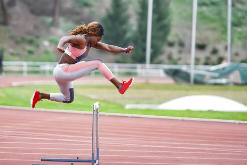 Young sportswoman jumping over hurdle during training - GGGF00057