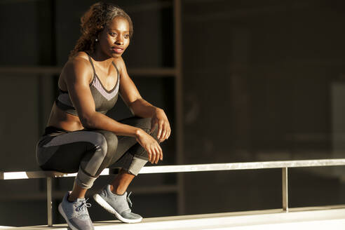Young woman in sports clothing sitting on railing in city - GGGF00080