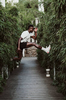 Sportsman jumping amidst plant - EBBF01352