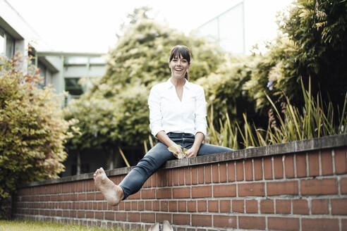 Smiling female professional sitting on retaining wall by plants at industry - JOSEF02141