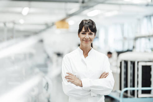 Smiling female scientist standing with arms crossed in bright laboratory - JOSEF02150