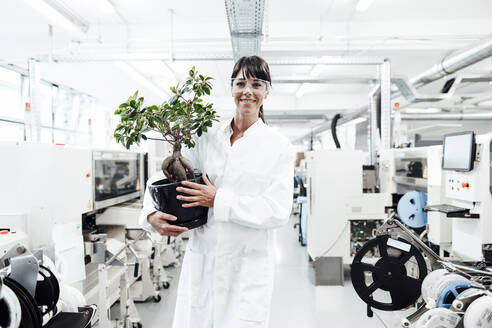 Smiling female scientist holding potted plant while standing amidst machineries at laboratory - JOSEF02177