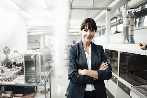 Confident businesswoman smiling while standing with arms crossed at industry - JOSEF02207