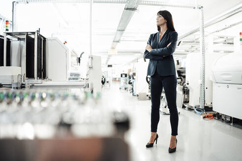 Thoughtful female professional looking away while standing with arms crossed at industry - JOSEF02219