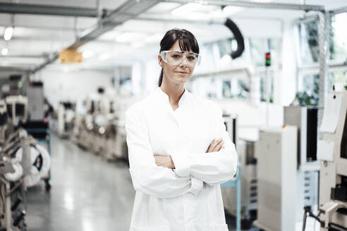 Confident female scientist standing with arms crossed in bright laboratory - JOSEF02243