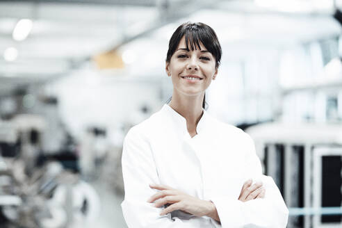 Smiling female scientist standing with arms crossed in bright laboratory - JOSEF02249