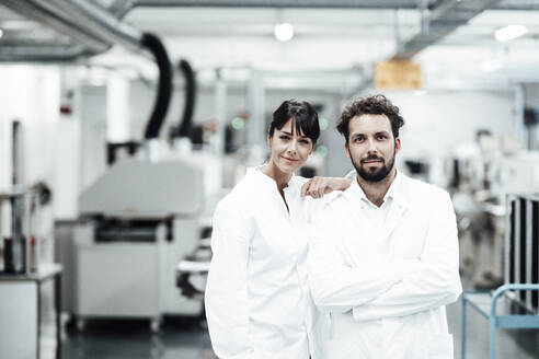 Male and female scientists in white lab coats standing at bright laboratory - JOSEF02252