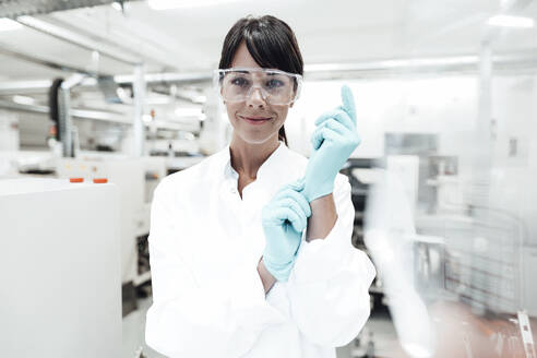 Smiling mature female scientist wearing gloves at laboratory - JOSEF02300