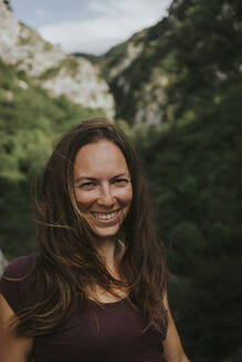 Smiling mid adult woman with long brown hair against mountain - DMGF00278