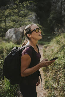 Woman looking away while holding smart phone for navigation during hiking on sunny day - DMGF00296