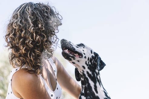 Young woman playing with Dalmatian dog on sunny day against sky - ABAYF00011