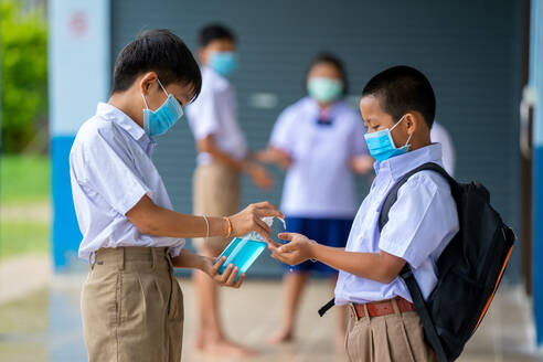 Asia elementary children spraying classmate's hands with disinfe - CAVF90513