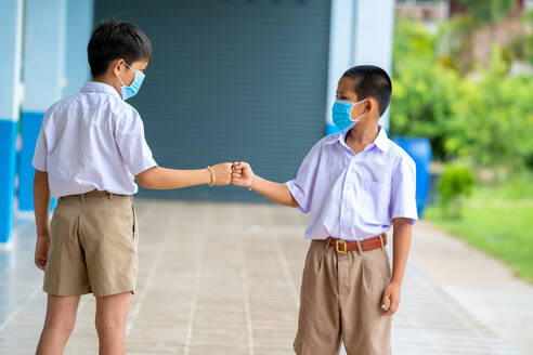 Asian children in school uniform wearing protective mask to Prot - CAVF90525