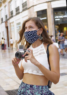 Young tourist woman photographs the city with her camera - CAVF90555