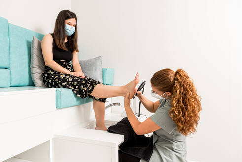 Side view of professional pedicure specialist polishing foot of female customer in protective mask with machine tool during appointment in modern apparatus cosmetology center - ADSF17197