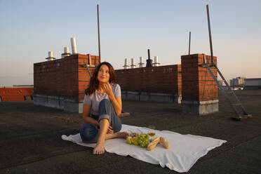 Thoughtful young woman having fruits during picnic on rooftop - NGF00704