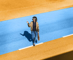 Young woman listening music through headphone while walking on yellow and blue street during sunny day - UUF22063