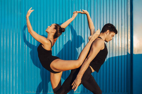 Professional gymnast couple doing attitude balance pose by blue wall - MIMFF00266