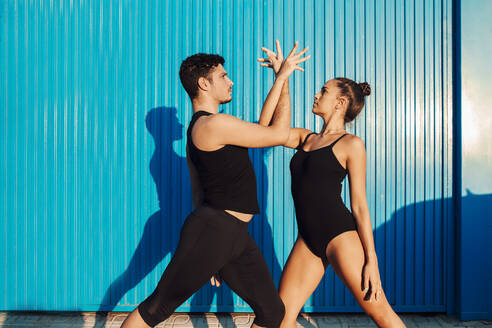 Young male acrobat helping female dancer in dance pose by blue wall - MIMFF00269