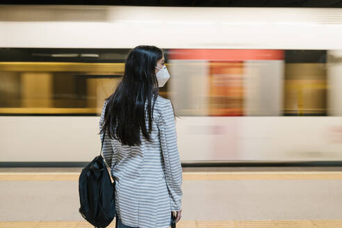 Woman waiting for her train at metro station during pandemic - EGAF00997