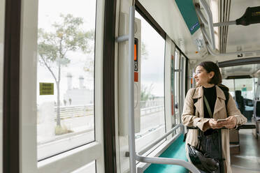 Woman with electric push scooter looking away while mobile phone in tram - VABF03984