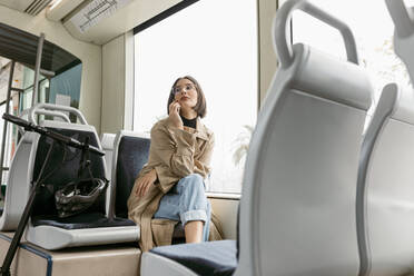 Woman looking away while sitting with electric push scooter in tram - VABF03987