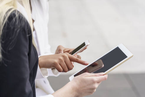 Businesswoman pointing at digital tablet while using mobile phone by colleague at city - GGGF00085