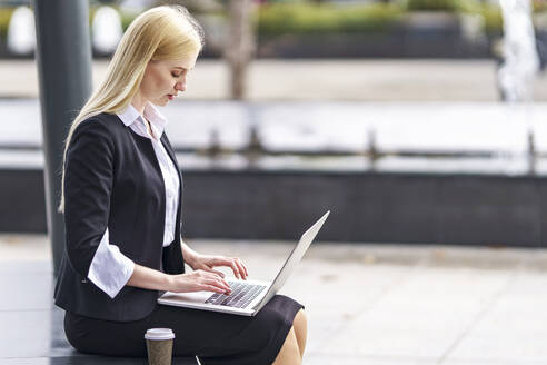 Blond businesswoman working on laptop while sitting on bench - GGGF00103