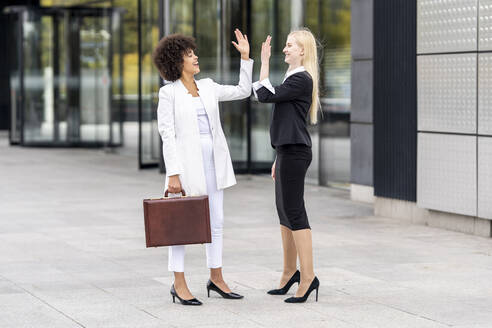 Businesswomen giving high five while standing on footpath - GGGF00130