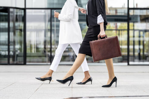 Businesswoman with briefcase using mobile phone while walking by colleague on footpath - GGGF00142