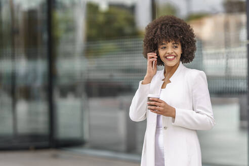 Smiling businesswoman talking on mobile phone while standing outdoors - GGGF00151