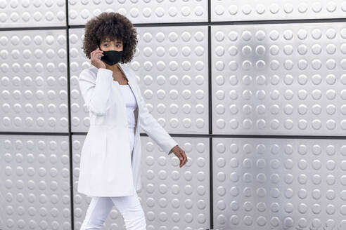 Businesswoman wearing face mask using mobile phone while walking against silver wall - GGGF00181