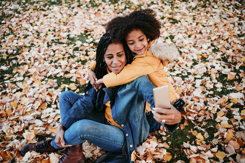 Girl embracing mother taking selfie through smart phone while sitting on autumn leaves - EBBF01428