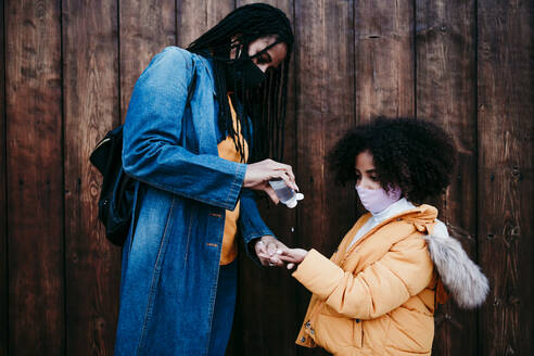 Mother giving alcohol hand sanitizer to daughter while standing against wooden wall - EBBF01440