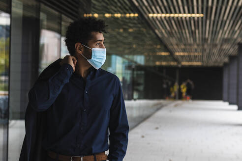 Businessman wearing protective face mask in city - PNAF00071