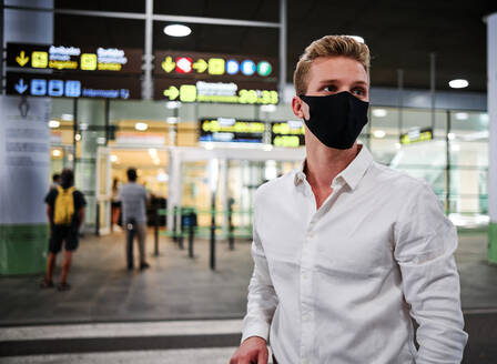 Serious male wearing protective mask standing in departure lounge of airport and waiting for flight during coronavirus epidemic while looking away - ADSF17441