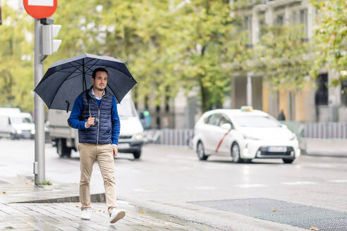 Young man walking on sidewalk with umbrella during rainy season - CJMF00355