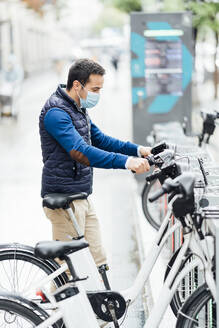 Young man wearing protective face mask holding electric bicycle at parking station during COVID-19 - CJMF00364