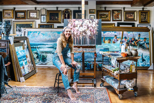Cheerful female artist in denim overall looking at camera while sitting near easel and painting in creative atelier - ADSF17606