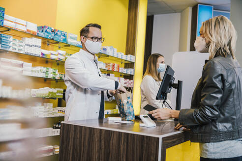 Female customer wearing face mask while making payment through smart phone at checkout counter in pharmacy - MFF06833