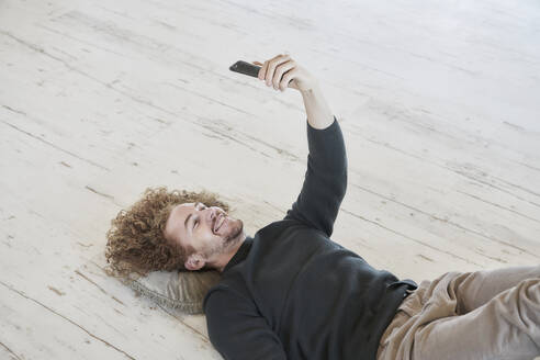 Smiling redhead man taking selfie through smart phone lying down on floor at home - FMKF06678