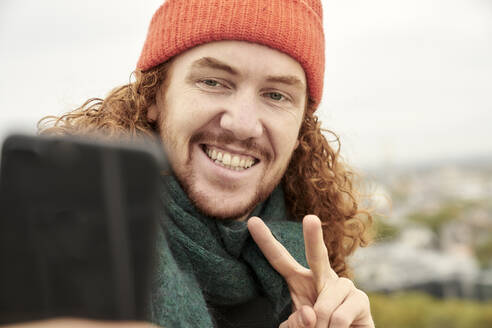 Smiling man doing peace sign while taking selfie on smart phone - FMKF06693
