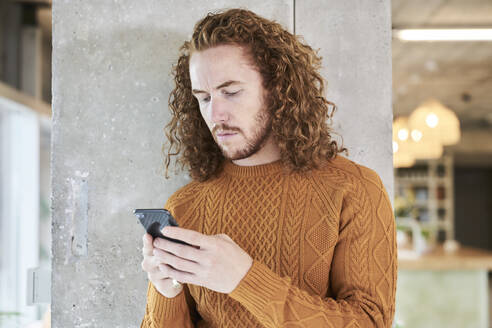 Hipster man text messaging on smart phone standing against gray column in living room at home - FMKF06714