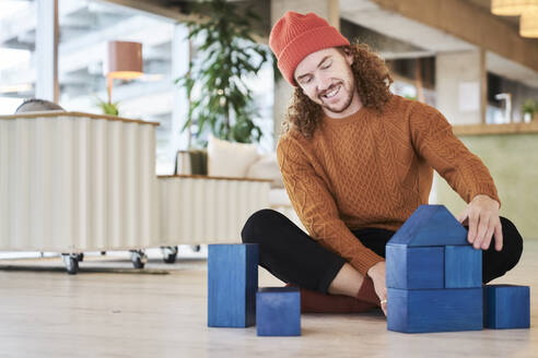 Hipster man playing with toy block while sitting on floor in living room at home - FMKF06720