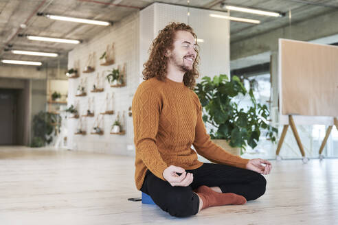 Smiling man meditating while sitting on floor in living room at home - FMKF06726