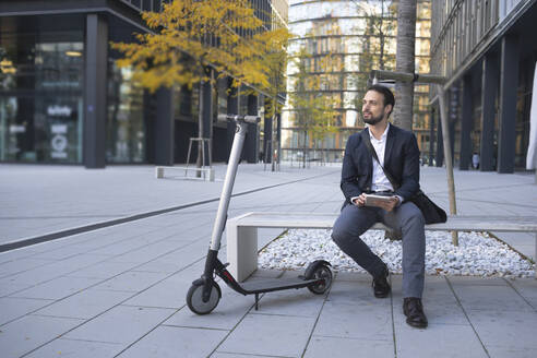 Businessman with digital tablet sitting by e-scooter on bench in city - HMEF01137